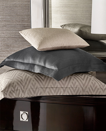 Three pillows of varying sizes in grey, cream & diamond-patterned