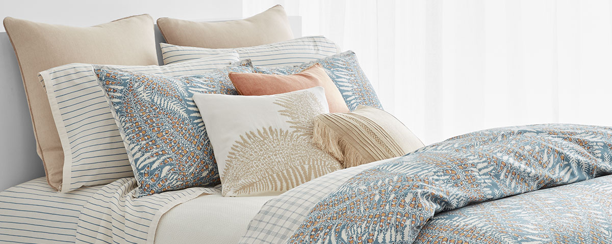 Bed with sheeting featuring feather motifs in a pastel palette