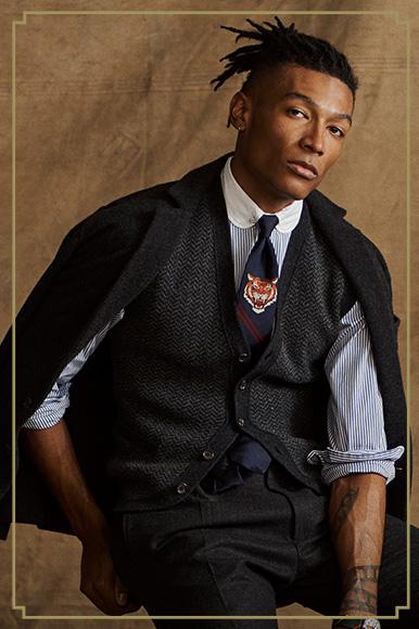Man in grey herringbone vest layered with striped dress shirt