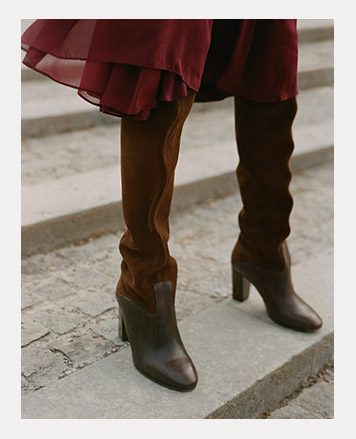 Woman wears brown leather boots under flowy red dress.
