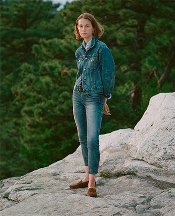 Woman in denim jacket & jeans standing on rock