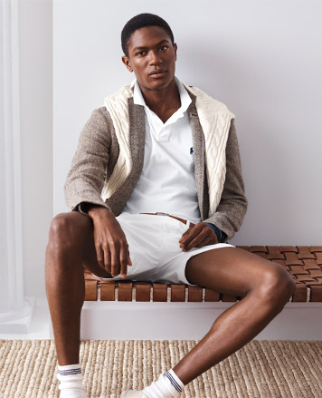 Man sitting on bench in white shorts paired with sport coat