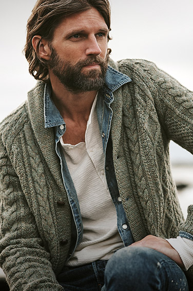 Man in waffle-knit Henley & denim shirt under cable cardigan