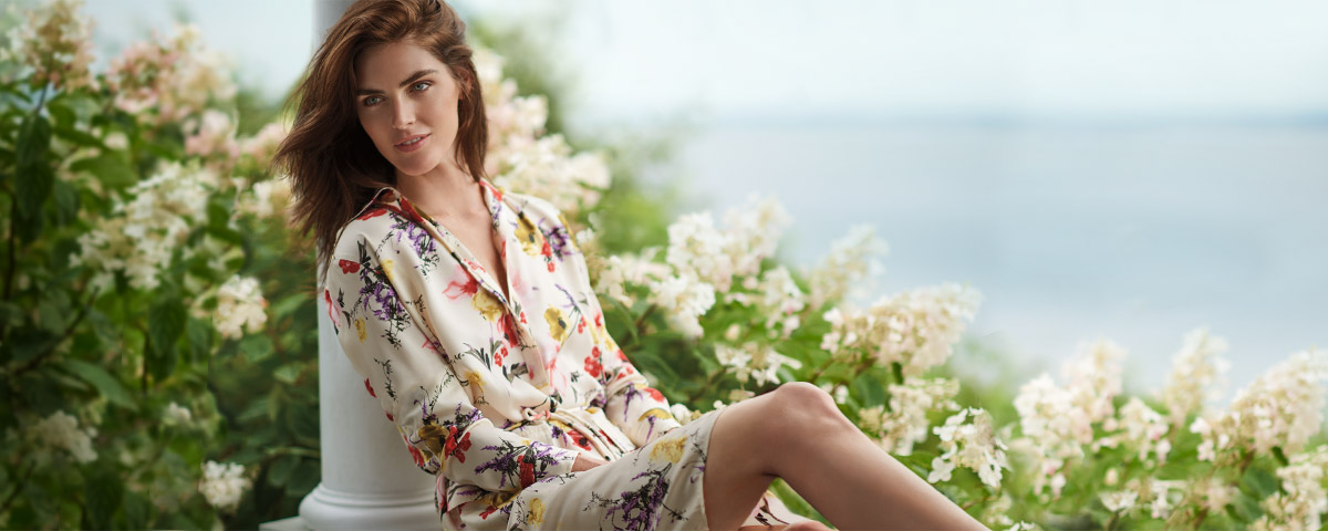 Model in white utility dress with bright floral print
