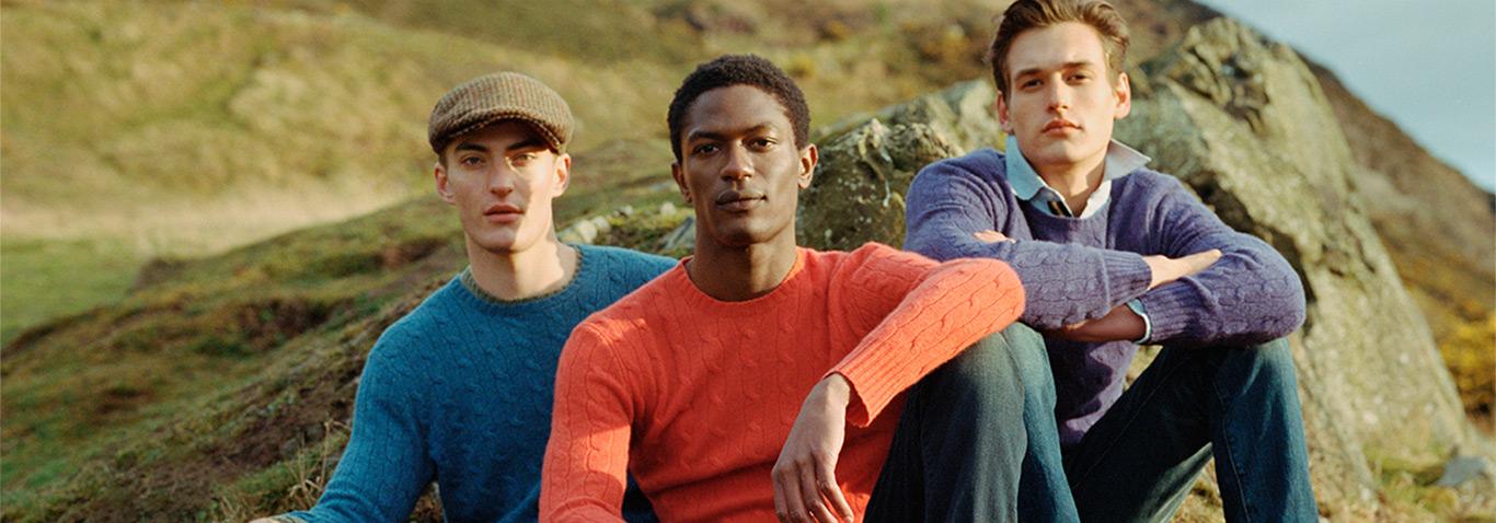 Men in blue, orange & purple sweaters in countryside
