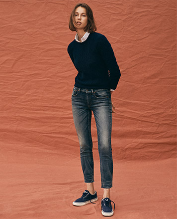 Woman in sweater & cropped jeans with fading