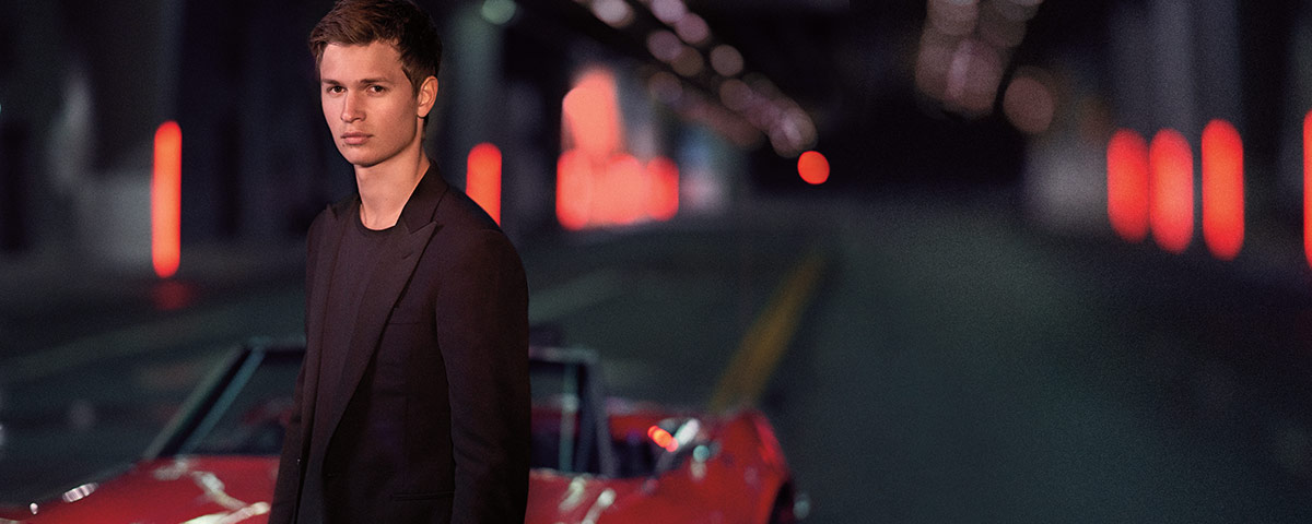 Ansel Elgort stands by red sports car