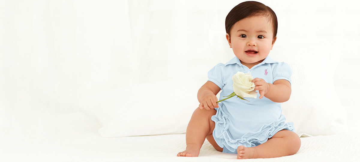 Baby wears light blue ruffled one-piece and holds white rose