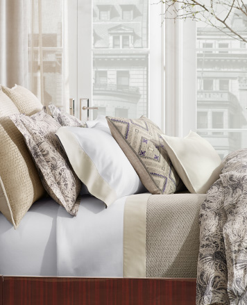 Bed appointed with neutral-hued damask-patterned comforter