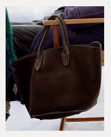 Brown suede tote bag hanging on arm of chair