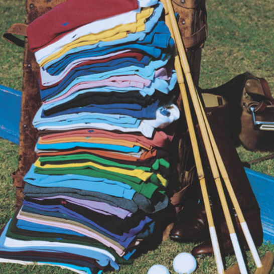 Stack of Polo shirts in various hues on polo field