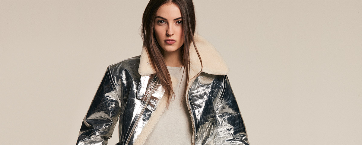 Model in metallic silver bomber jacket with shearling collar