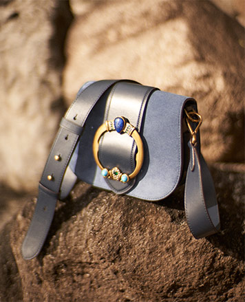 Blue suede shoulder bag with large jeweled buckle at front