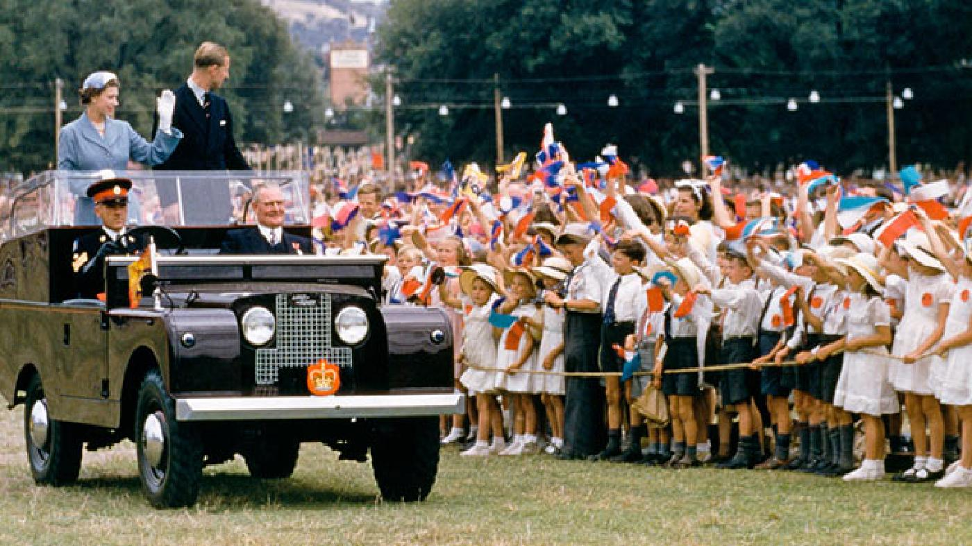 From the back of a Defender during a royal tour in 1954, Queen Elizabeth II and her husband, Prince Philip, wave to a crowd of children in New South Wales, Australia