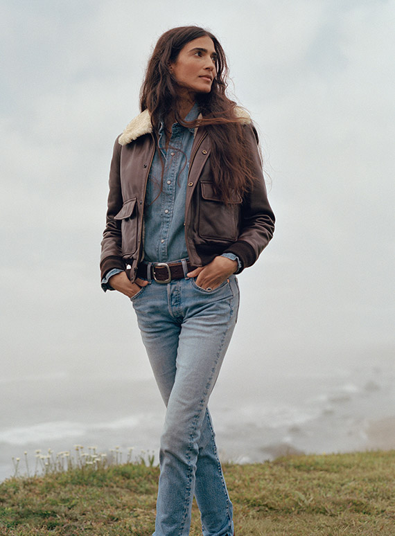 Woman in jeans, shearling-lined bomber jacket & chambray shirt