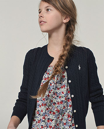 Girl wears cardigan over floral shirt.
