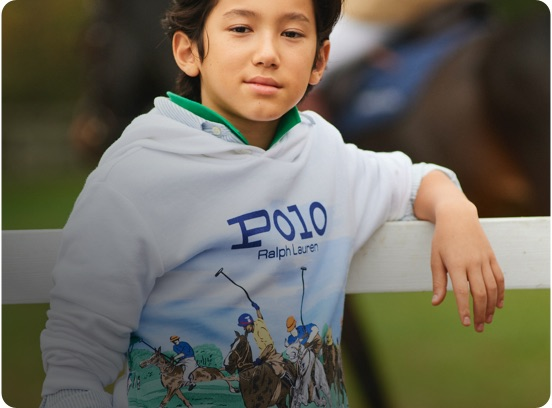 Boy in white hoodie with polo match print at front.