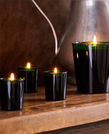 Candles in green glass vessels of various sizes