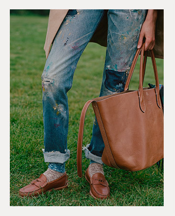 Close-up of model wearing ripped-and-repaired denim with loafers.