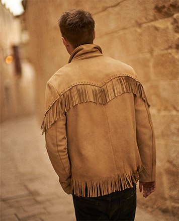 Man in tan leather jacket with fringe at yoke & hem