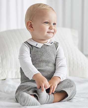 Baby boy wears grey top with Peter Pan collar.
