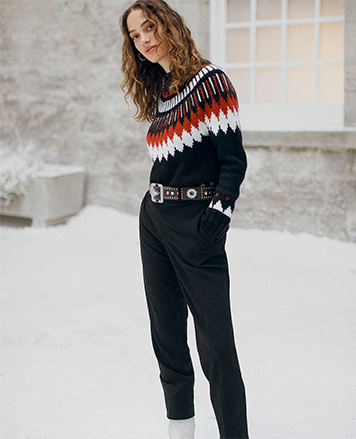 Woman in black pants & sweater with red & white Southwestern motif