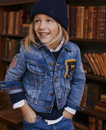 Boy wears denim jacket with patches.