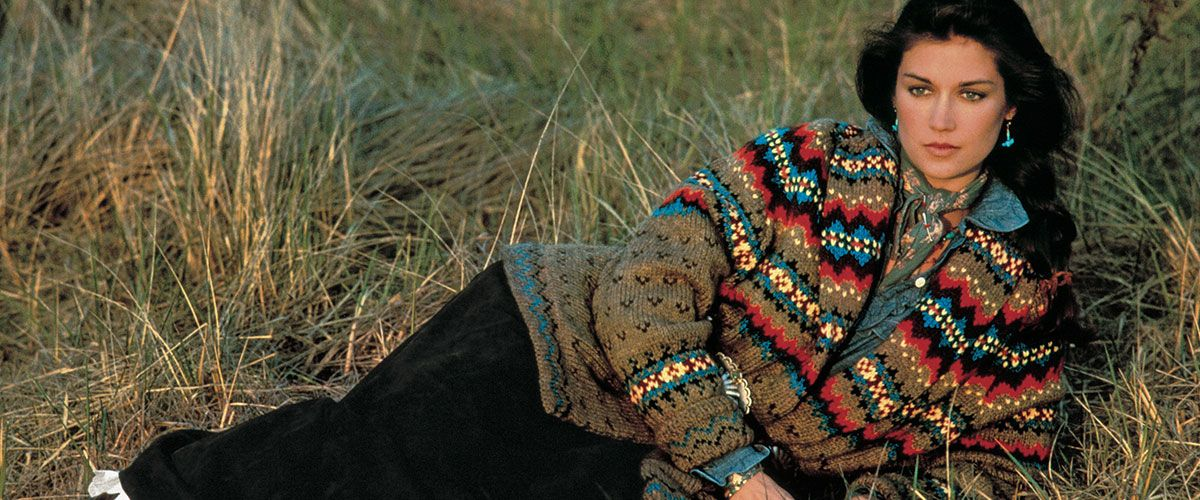 Women lies in grass in cardigan with a bold Southwestern motif