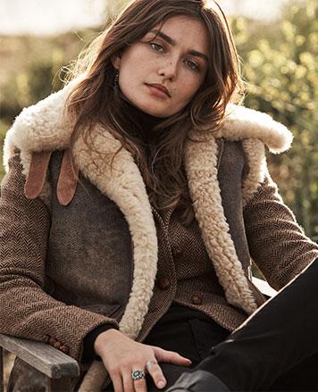 Woman in shearling vest layered over herringbone blazer