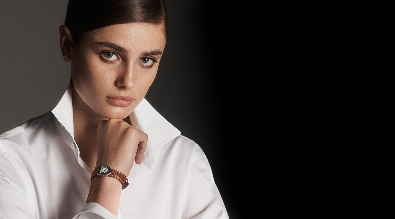 Model wears watch with stirrup-inspired silhouette & brown leather strap