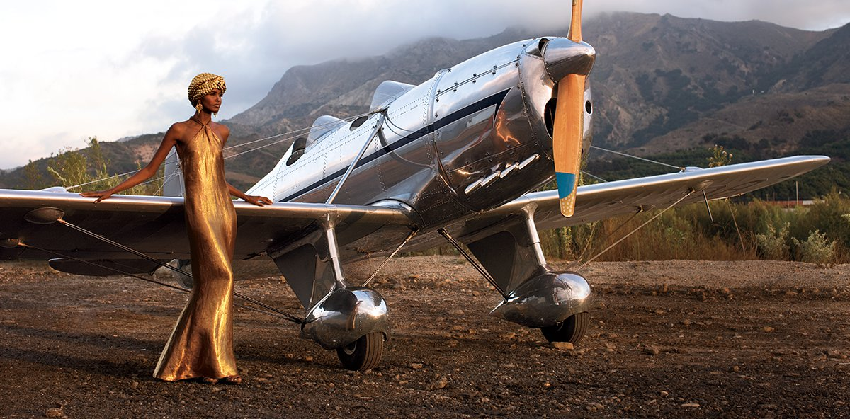 Model wears gold gown and turban while leaning against old-fashioned airplane.