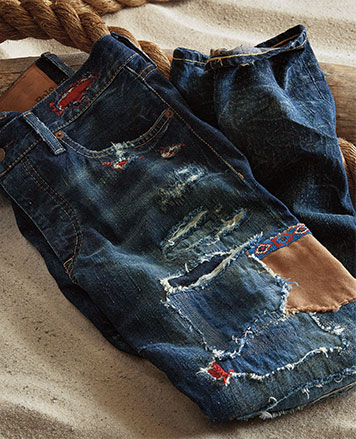 Close-up photo of distressed and patched jeans