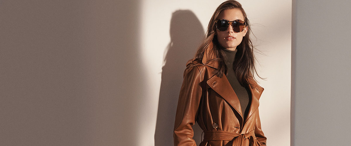 Woman in rich brown leather trench coat & tortoiseshell sunglasses