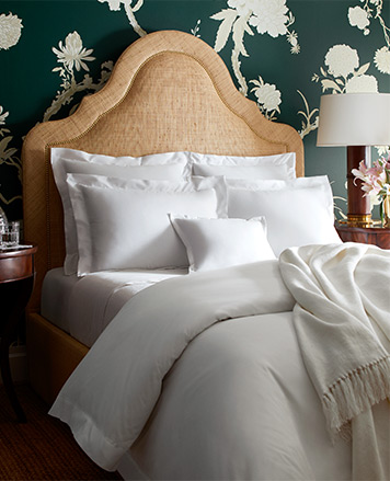Bed made with crisp white comforter, sheets & pillows
