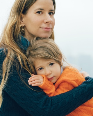 Mother and child wear navy and orange cable-knit sweaters.