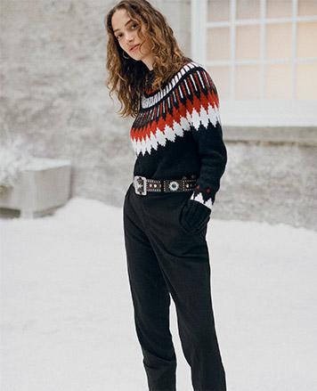 Woman in wide-leg black pants & plaid ruffled top