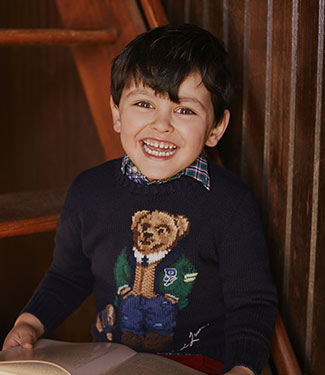 Boy wears navy sweater with Polo Bear at chest.