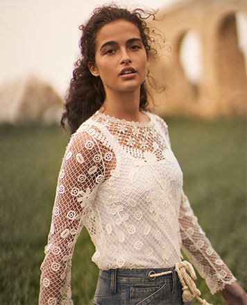 Woman in lace top with floral embroidery & scalloped trim