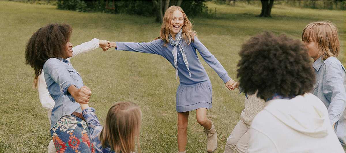 Kids in Polo attire hold hands in a circle.