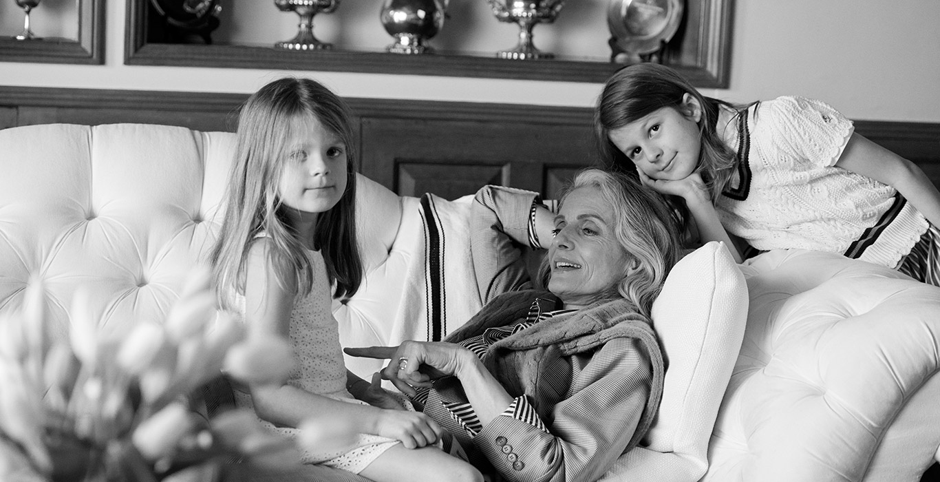 Woman in blazer & striped shirt with granddaughters