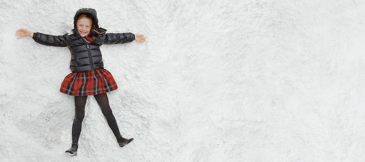 Girl makes a snow angel while wearing tartan dress and black puffer jacket.