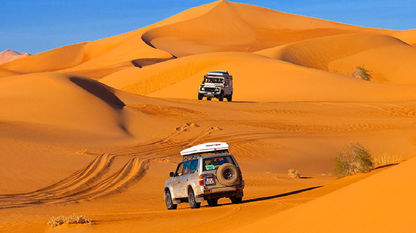A Defender (top) and a Toyota make tracks in the Sahara Desert's Ubari dunes
