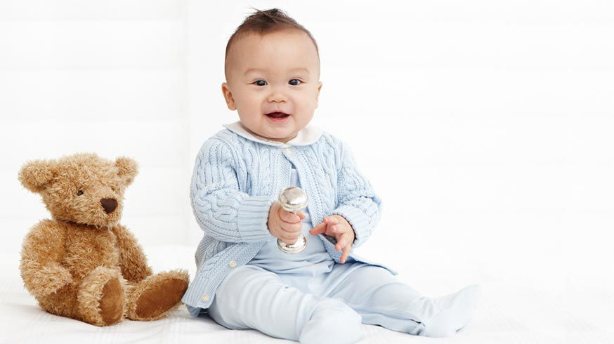Baby wears blue cable-knit cardigan over matching footed coverall