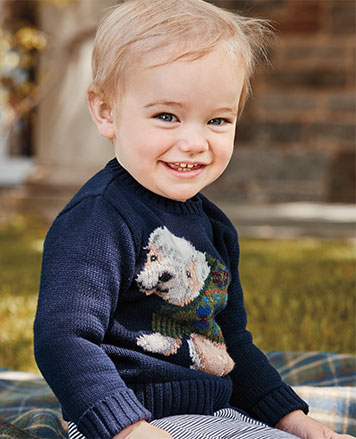 Baby boy wears intarsia-knit dog sweater and striped leggings.