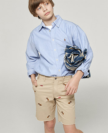 Boy wears embroidered chino shorts with light blue button-down.