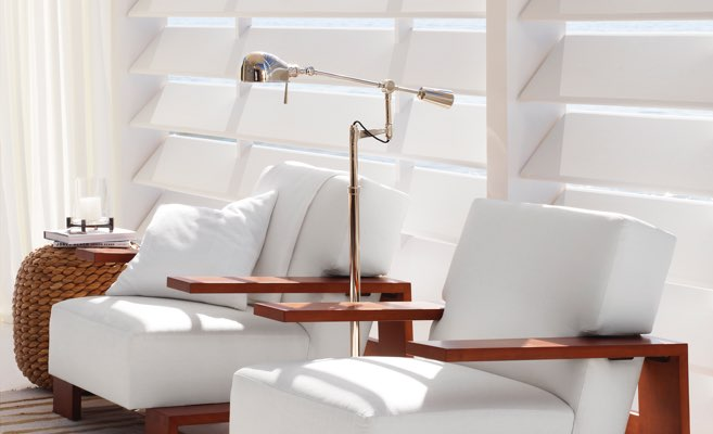 Metal boom-arm lamp between two wooden chairs with white cushions.