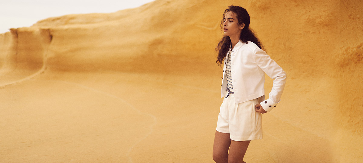Woman wears white shorts, white jacket, and striped tee in desert.