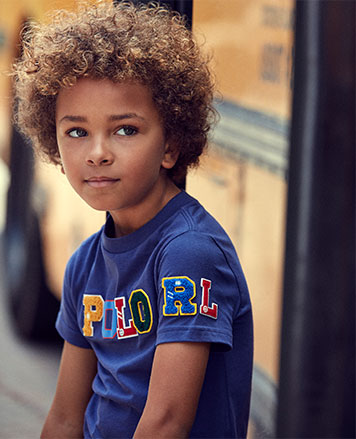 Boy wears blue T-shirt with Polo patches at chest.