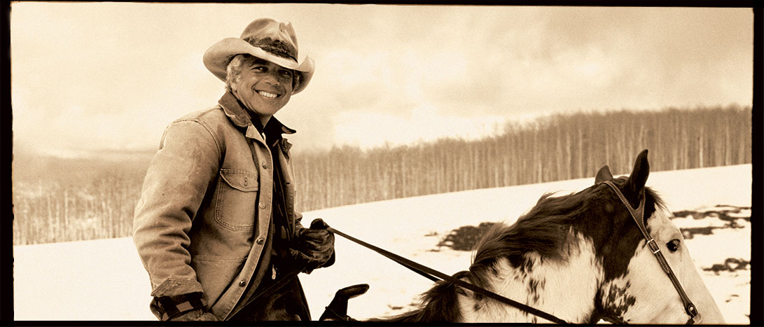 Sepia-tone photograph of Ralph Lauren riding horse.