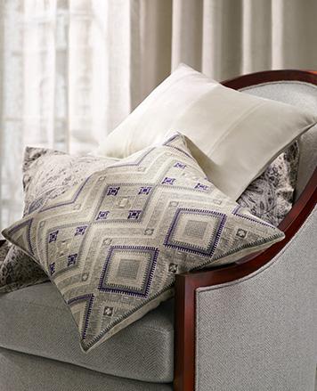 Throw pillows with geometric grey & purple motifs